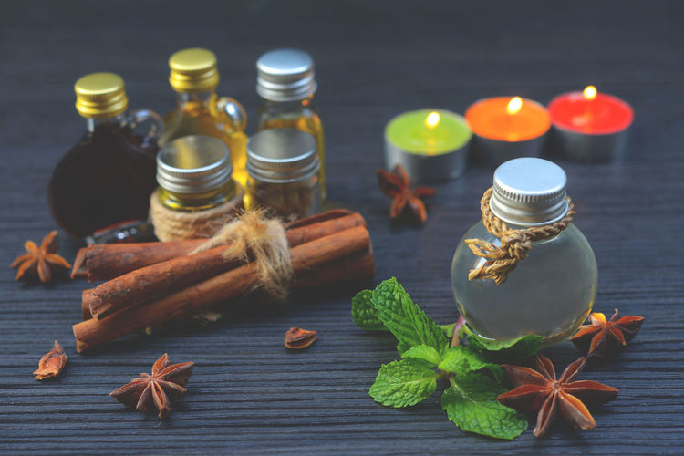 Close-up of oils with spices and herbs on table