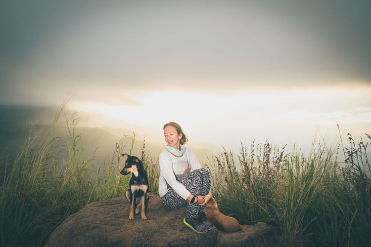 Woman with dog sitting on rock against sky