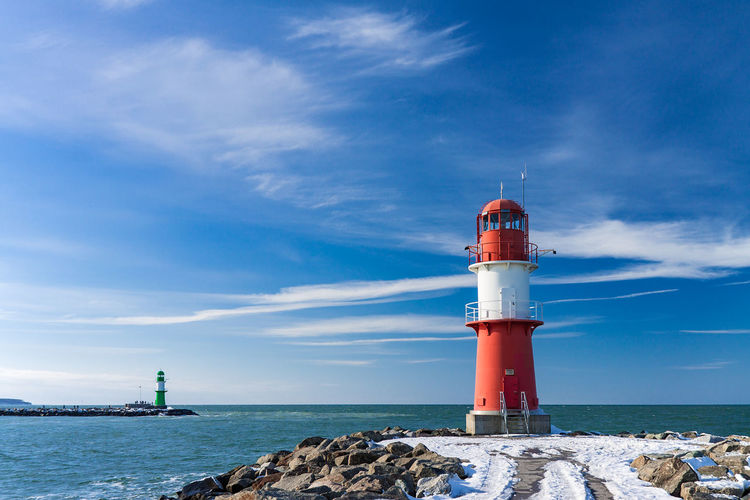 Lighthouse by sea against blue sky