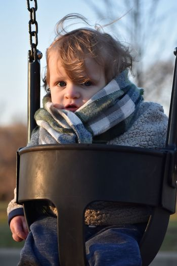 Portrait of cute baby boy sitting on swing in park during winter
