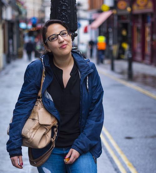 Portrait of woman standing on street in city