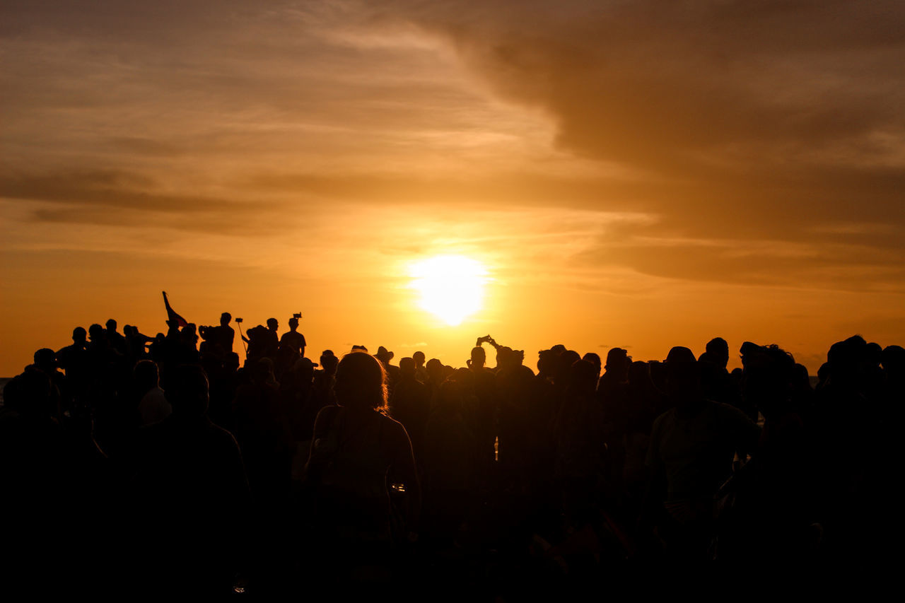 Silhouette Crowd Against Cloudy Orange Sky During Sunset