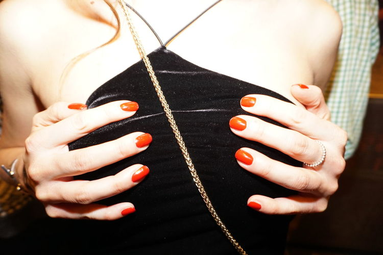 Midsection of young woman with hands on chest