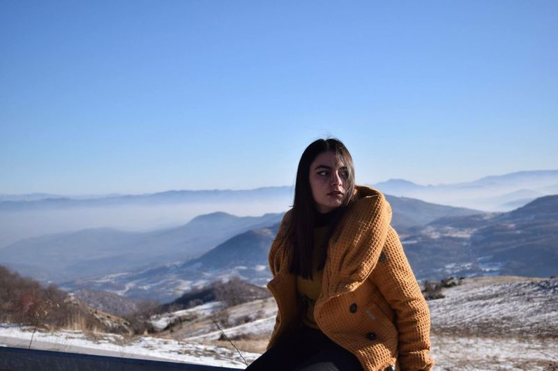 Young woman sitting on cliff against mountains during winter