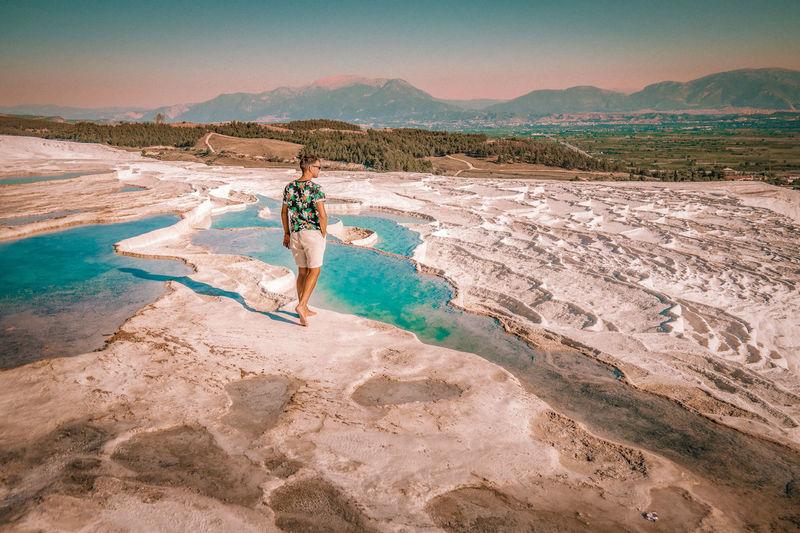 Full length of man walking on salt flat against sky