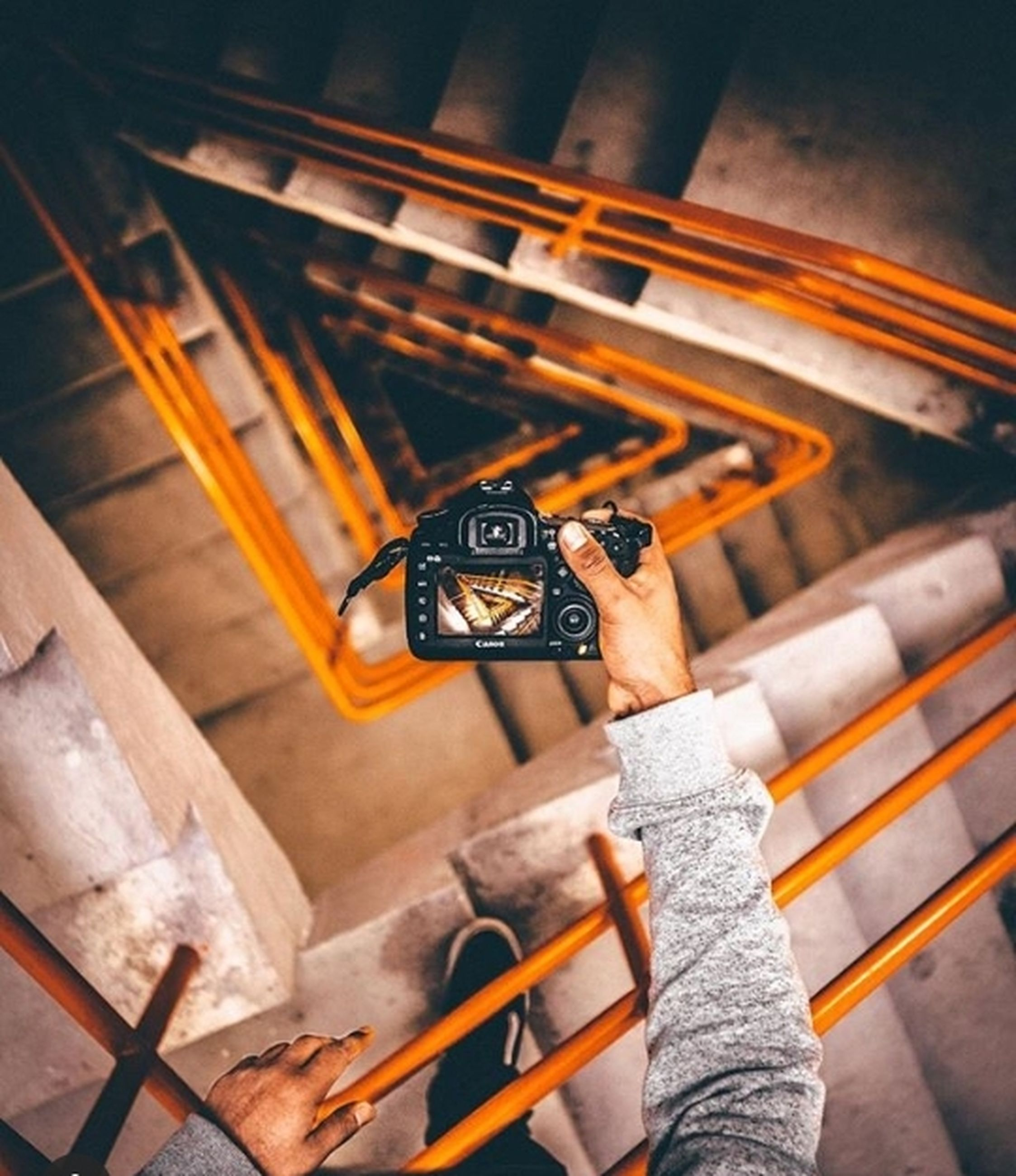 holding, one person, technology, high angle view, human hand, real people, focus on foreground, human body part, indoors, hand, wood - material, photography themes, camera - photographic equipment, unrecognizable person, close-up, day, directly above, retro styled, photographer