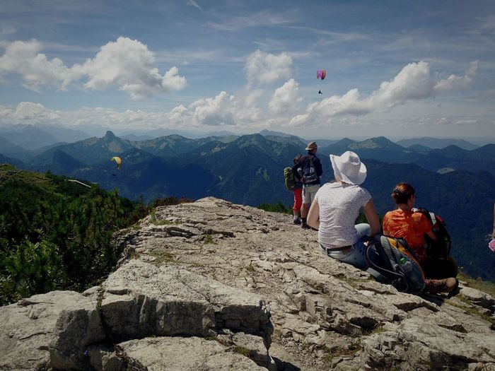 People sitting on cliff by mountains against sky