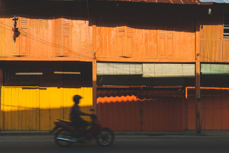 Lowlight photography light shadow - motion blur of man on a motorbike in front closed shop houses