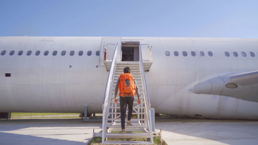 Rear view of man climbing on abandoned airplane against sky