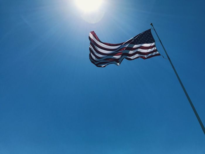 Low angle view of flag flying against blue sky