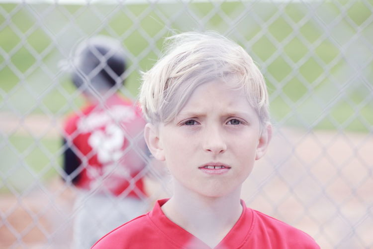 Baseball Junior  Red Baseball - Sport Baseball Field Blond Hair Boys Child Childhood Day Fence Front View Hair Headshot Innocence Leisure Activity Lifestyles Males  Outdoors Portrait Pre-adolescent Child Real People Sport Team Team Sport