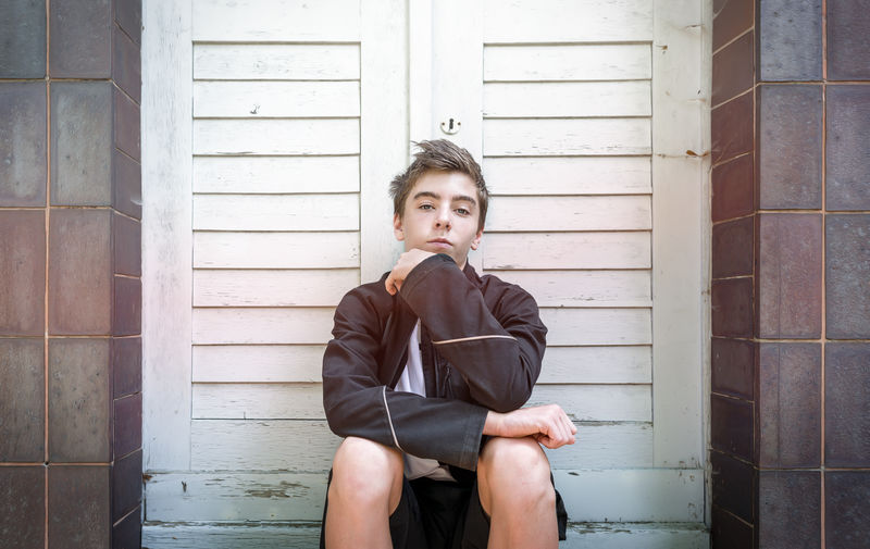Portrait Of Confident Teenage Boy Sitting Against Closed Doors