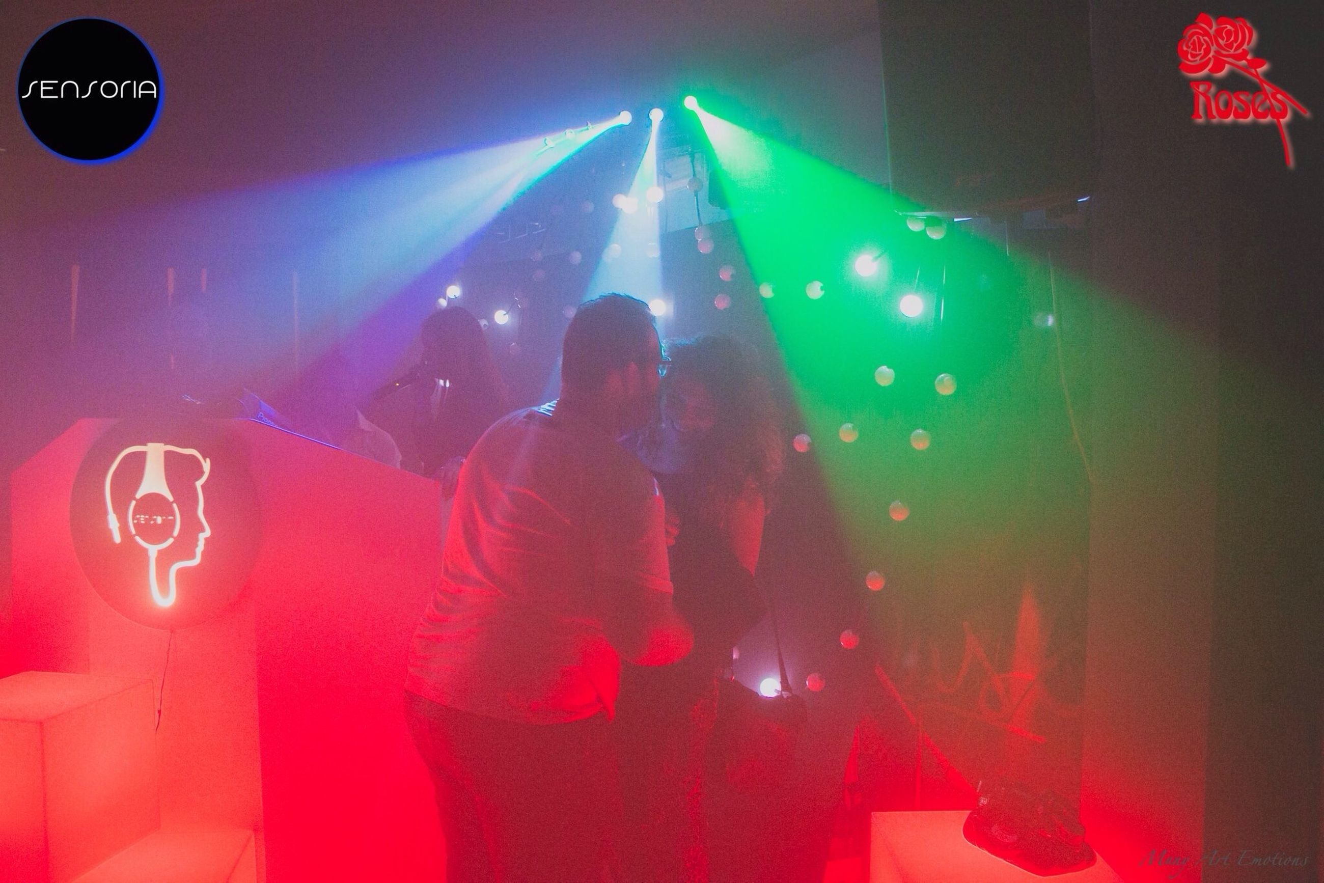 illuminated, indoors, night, celebration, lighting equipment, red, communication, arts culture and entertainment, nightlife, men, leisure activity, text, lifestyles, human representation, light - natural phenomenon, performance, multi colored, neon, unrecognizable person