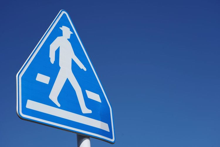 Pedestrian Crossing Pedestrian Sign Pedestrian Walking Blue Blue Sign Communication Road Sky No People Clear Sky Road Sign Arrow Symbol Guidance Safety Symbol Information