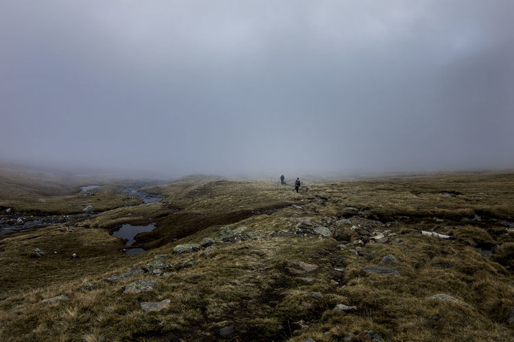 Two hikers disappearing in the thick fog Hiking Activity Adventure Beauty In Nature Cloud - Sky Clouds Eerie Environment Fog Foggy Get Lost Hiking Land Landscape Leisure Activity Moody Mountain Nature Outdoors Remote Scenics - Nature Sky Tranquility