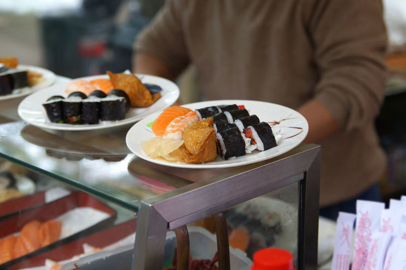 Midsection Of Man Having Sushi At Restaurant