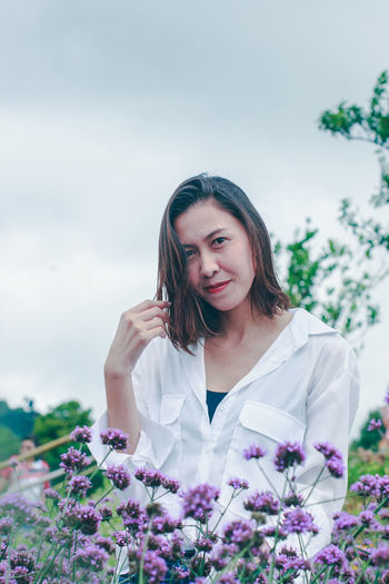 Beautiful woman with pink flower against sky