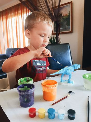 Little boy coloring dinosaur Art And Craft Artistic Child How Do We Build The World? Creative Education Family Hobby Hobbyphotography Home Interior Indoors  Kid Kids Kindergarten Learning Little Boy Paint Paint Brush Paint Bucket Painting Portrait Preschool Table Toddler