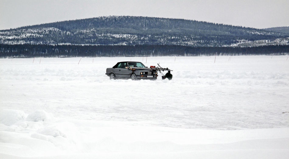 Car With Television Camera On Snowy Field Against Mountain