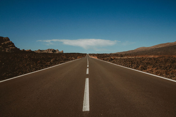 Empty road along landscape and blue sky
