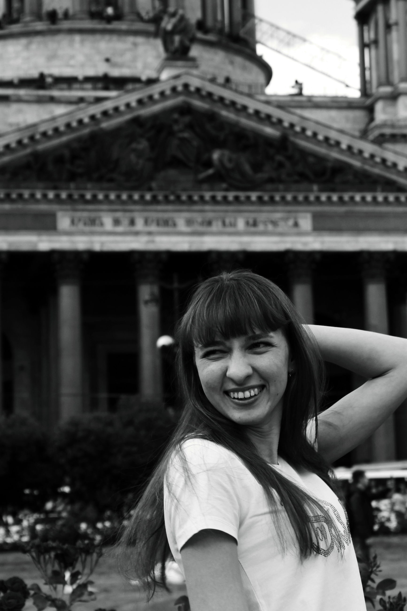 portrait, real people, happiness, one person, smiling, architecture, long hair, hair, emotion, hairstyle, looking at camera, built structure, building exterior, focus on foreground, lifestyles, teeth, women, toothy smile, young adult, headshot, beautiful woman, outdoors, bangs