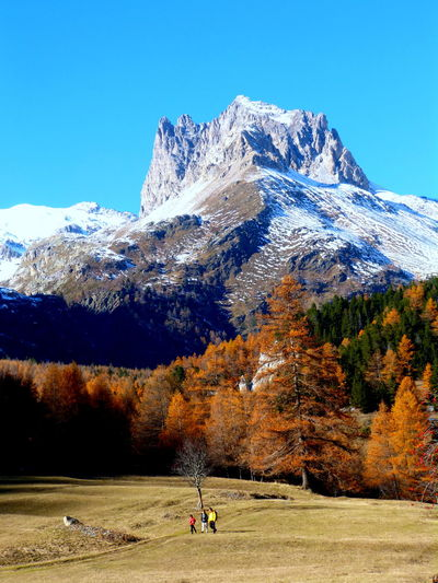 Snowcapped mountains and landscape against blue sky during autumn at european alps