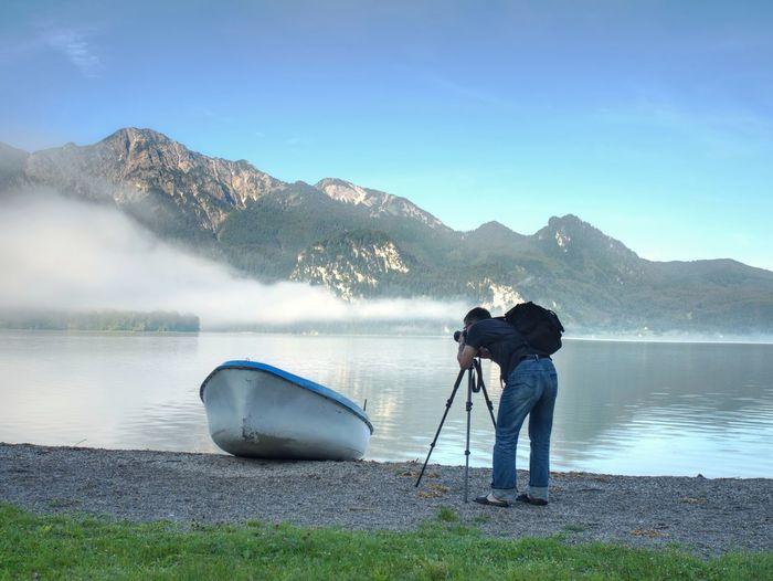 Man hiker is taking photo of ship at mountain lake shore. silhouette at fishing paddle boat at lake