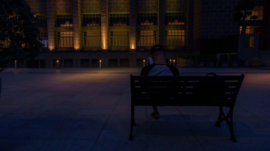Man sitting on bench in illuminated building at night