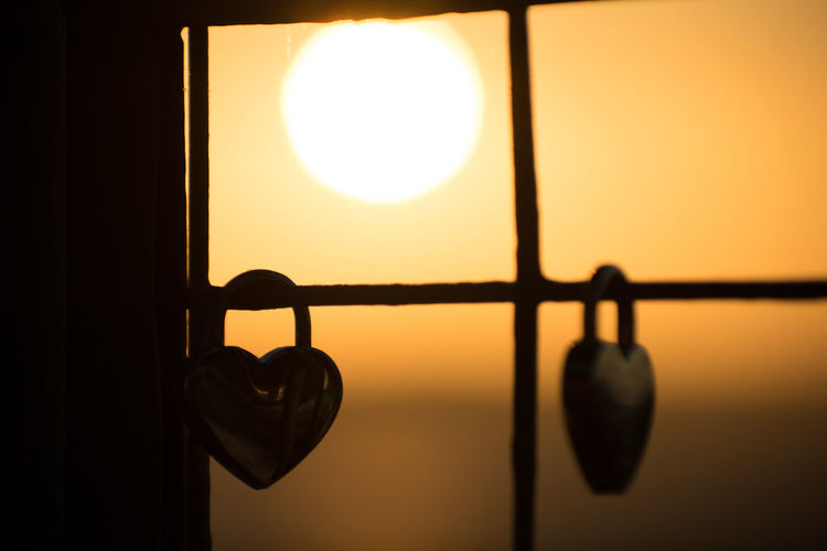 Close-up of silhouette hanging light against window