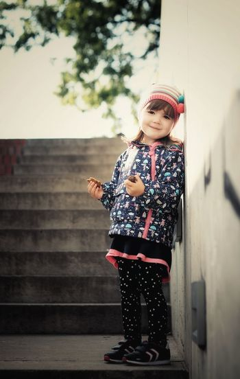Happy girl with cookies standing on steps