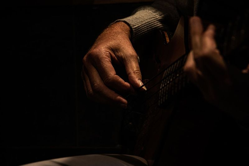Midsection of man playing guitar in darkroom