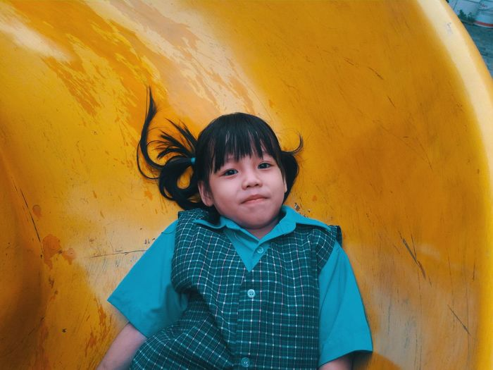 Portrait of cute girl on yellow slide