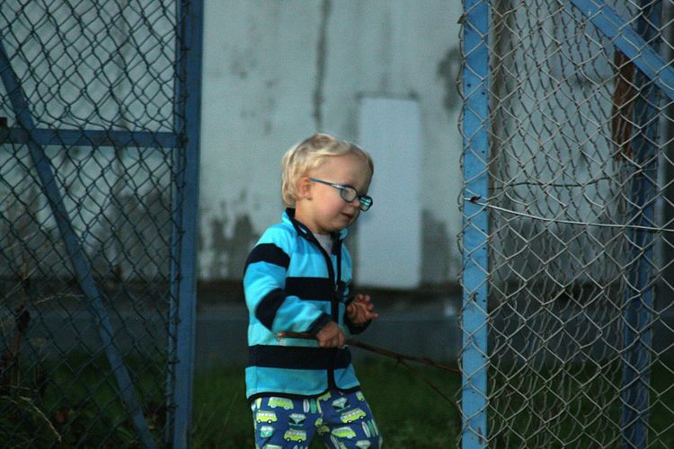 Cute boy standing by chainlink fence