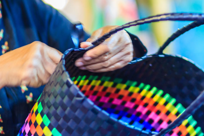 Close up hand of weaver during weaving basket made from plastic fiber. Weaver is weaving plastic basket show to the tourist in Bangkok, Thailand. Market Market Vendor Plastic Bag Weave Weaves Adult Art And Craft Basket Basket Weave Close-up Cutting Day Human Body Part Human Hand Indoors  Making Marketplace Multi Colored Needle Occupation One Person People Plastic Plastic Baskets Real People Sewing Skill  Weaver Weaving Working Workshop