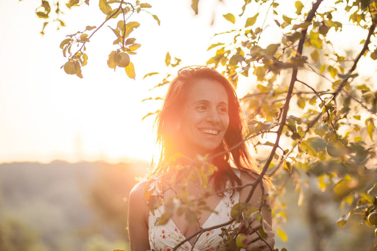 Smiling mature woman standing by tree against sky during sunset