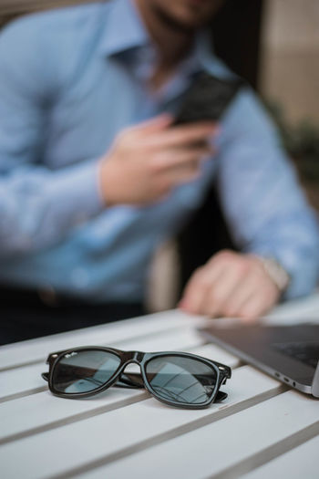 Close-up of sunglasses against businessman using mobile phone on desk
