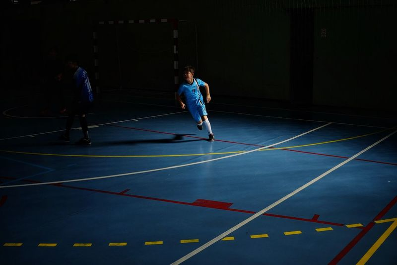 Indoors  Sports Football Soccer Gametime Ball Playing Games Lightandshadows Blue Full Length Sportsman Sports Clothing Sport Men Athleticism Competition Sprinting Goal Post Soccer Player Kids' Soccer Soccer Ball Soccer Goal Soccer Field