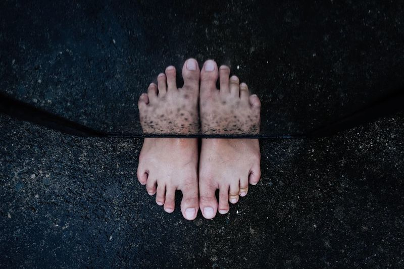 High angle view of human feet on sand