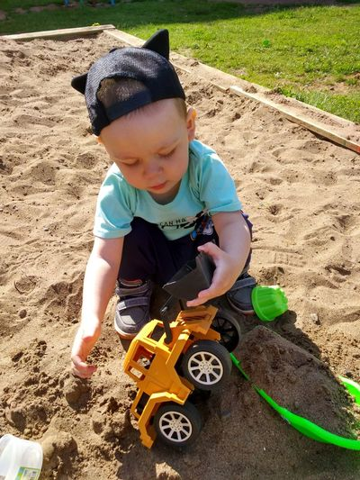 High angle view of boy playing with construction toys in sandbox at playground