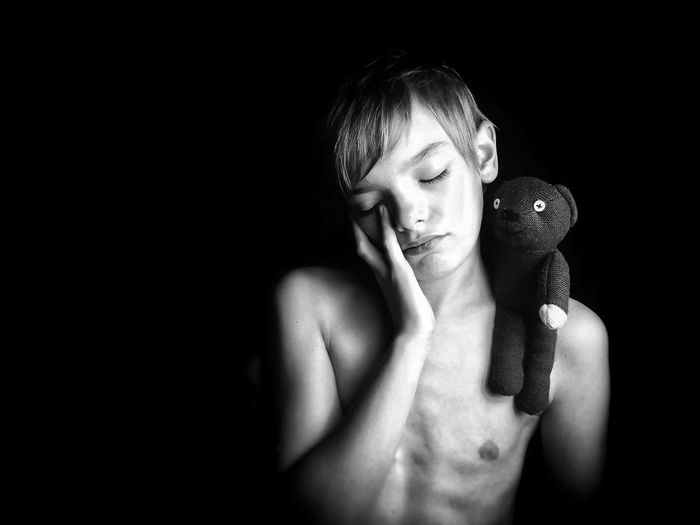 Shirtless boy with toy standing against black background