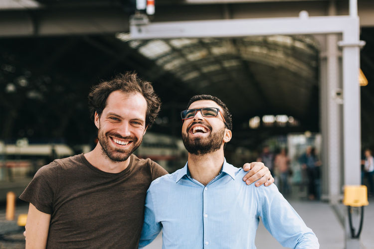 Happy friends laughing while standing at railroad station platform