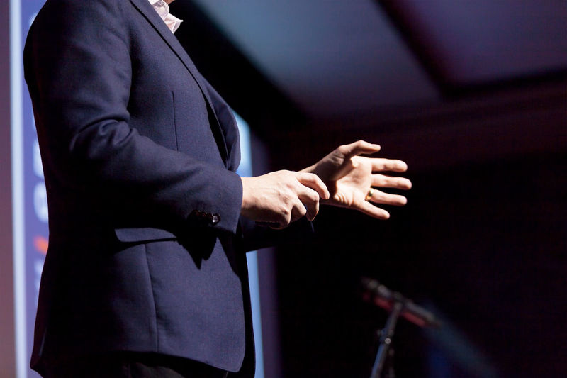 Gesturing presenter at a business conference or similar corporate event. Corporate Business Business Business Person Suit Businessman Conference - Event Presentation Coach Coaching Life Coach Speaker Speech Training Expert Educator Knowledge Body Language Communication Information Publicity Image Lecture Lecturer Explaining  Event Gesturing