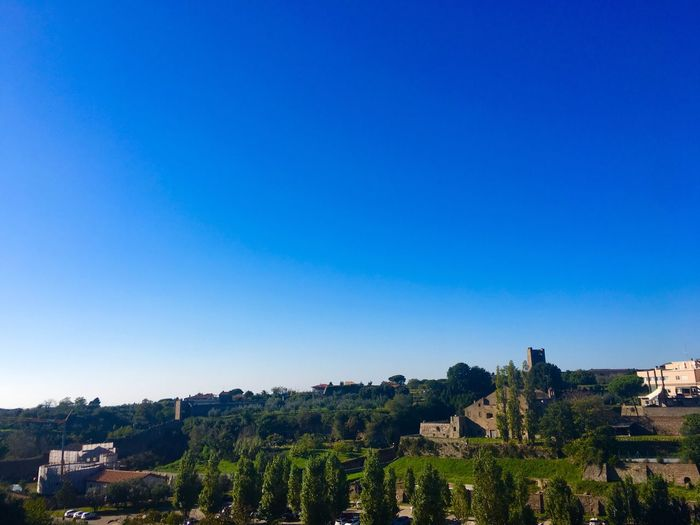 Scenic view of townscape against clear blue sky