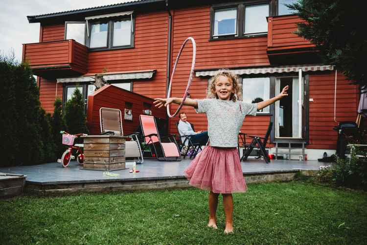 Portrait of a smiling girl standing outside house