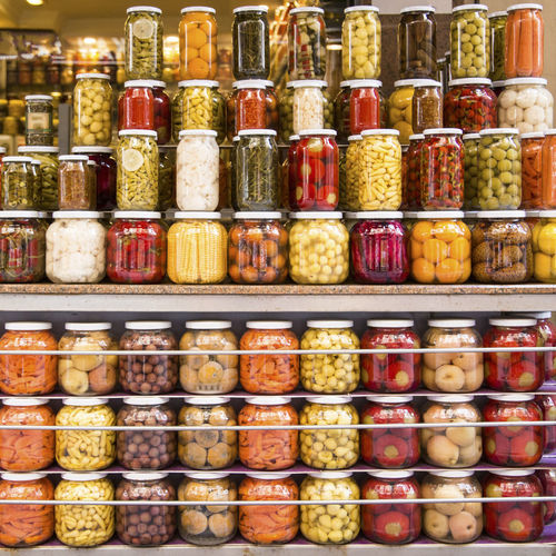 Pickles In Glass Jars Arranged On Shelves At Market For Sale