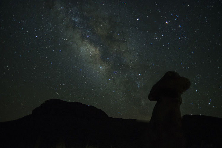 Silhouette mountains against star field at night