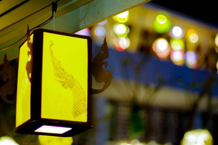 Low Angle View Of Illuminated Lighting Equipment Hanging At Night