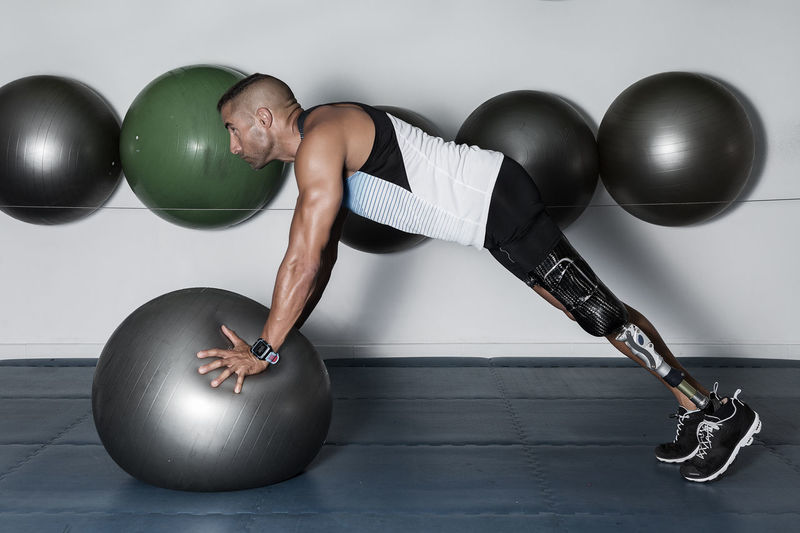 Side view of concentrated sportsman with leg limb training with medicine ball in gym Athletic Determination Man Modern Amputation Artificial Balance Ball Confident  Disability  Fitness Focused Gym Healthy Lifestyle Indoors  Lifestyles Limb One Person Prosthesis Push-ups Sport Sports Equipment Strength Training Workout