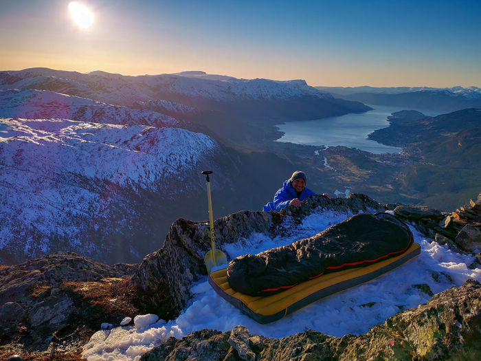 Explorer and sleeping bag on top of snow capped mountain