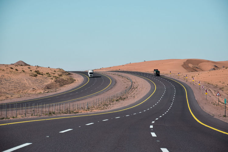 Road passing through desert against clear sky